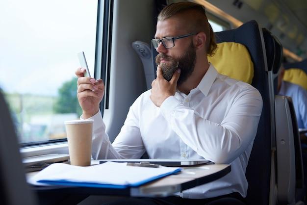 Zakenman die mobiele telefoon bekijkt