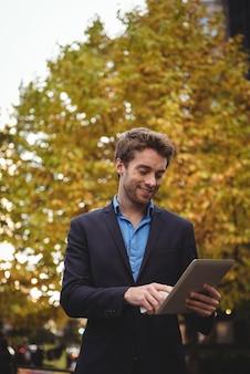 Zakenman die mobiele telefoon houdt en digitale tablet gebruikt