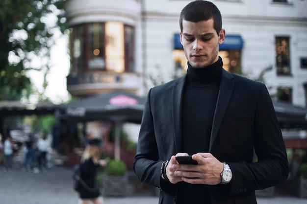 Zakenman die mobiele telefoon houdt en het in openlucht bekijkt