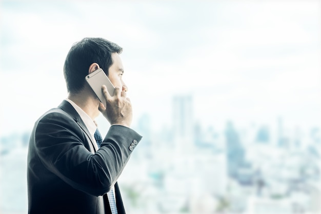 Zakenman die mobiele telefoon met behulp van die door bureauvenster kijkt