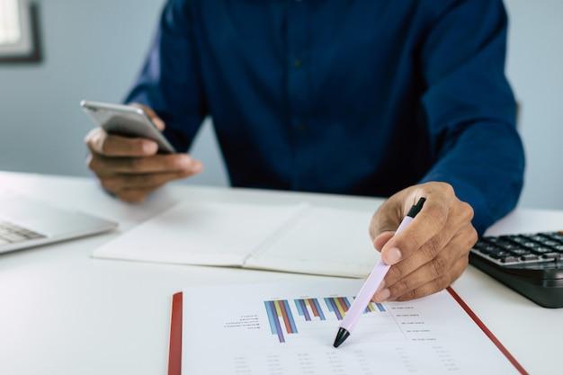 Zakenman die mobiele telefoon met behulp van die over financiën met documentrapport thuis berekenen over bureau