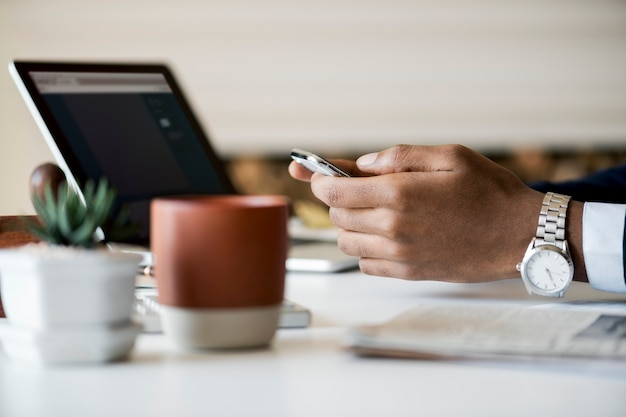 Zakenman die mobiele telefoon met behulp van op het werk