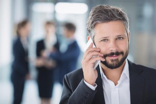 Zakenman die mobiele telefoon met behulp van