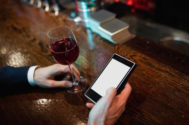 Zakenman die mobiele telefoon met in hand glas rode wijn met behulp van