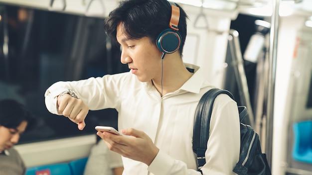 Zakenman die mobiele telefoon op openbare trein met behulp van