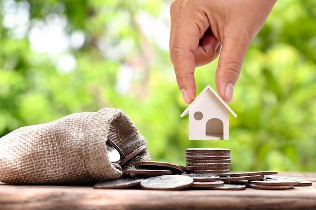 Zakenman die modelhuis op een stapel munten van het investeringsconcept houdt hypotheek en woningbouwrente interest