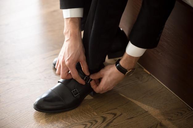 Zakenman die modieuze schoenen draagt wanneer op het werk gaan