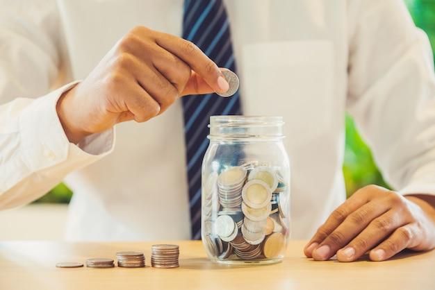 Zakenman die muntstukken in glas zet. geld besparen concept.