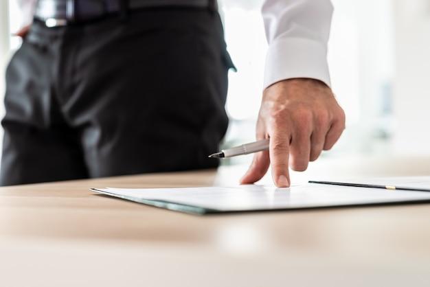 Zakenman die naast zijn bureau staat met een pen die op een document of inschrijvingsformulier wijst naar waar de handtekeningregel is.