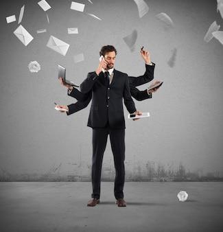 Zakenman die om problemen op te lossen multitasking wordt met vellen en letters aan de muur