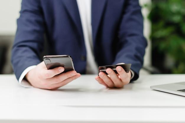 Zakenman die online betalingen verrichten en geld van creditcard bedraden die smartphone gebruiken