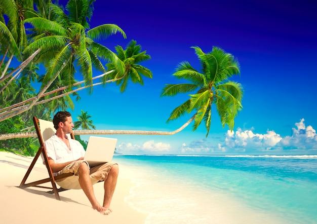 Zakenman die op afstand van een strand werkt