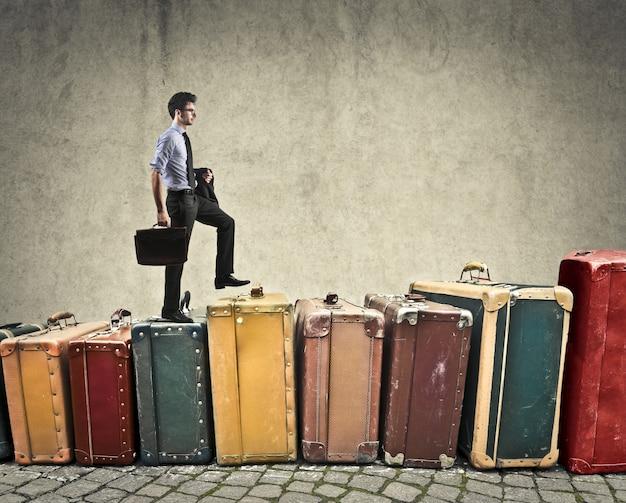 Zakenman die op bagage beklimt