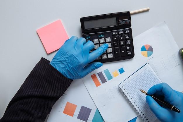 Zakenman die op bureau in beschermende handschoenen werkt. werken met laptop en rekenmachine en iets van een idee noteren