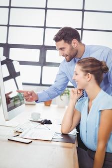 Zakenman die op computer richt terwijl het verklaren van vrouwelijke collega