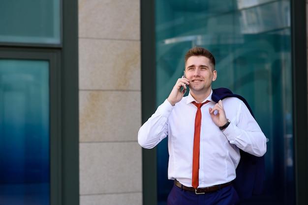 Zakenman die op de telefoon en het glimlachen spreekt.