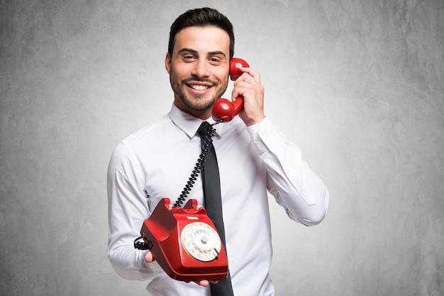Zakenman die op de telefoon spreekt. grijze concrete achtergrond