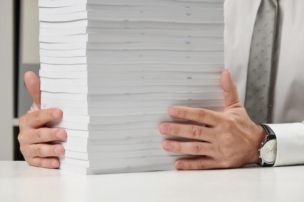 Zakenman die op een kantoor werkt, leest stapel boeken en rapporten. bedrijfsconcept financiële boekhouding.
