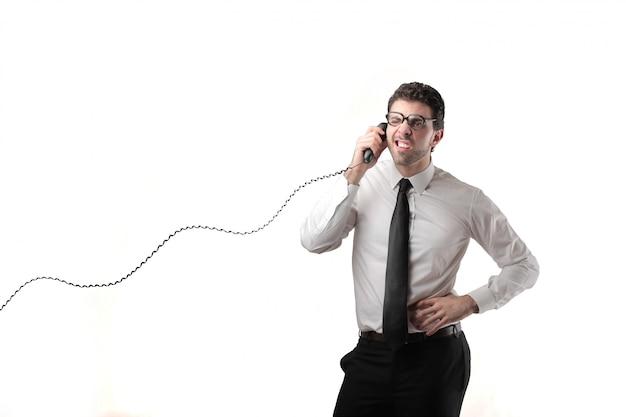 Zakenman die op een klassieke telefoon spreekt