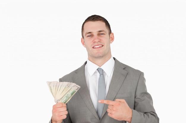 Zakenman die op een pakje van contant geld richt