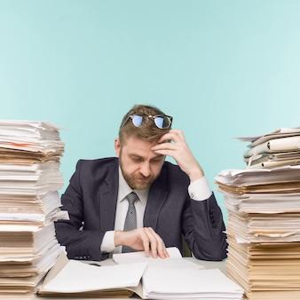 Zakenman die op kantoor werkt en stapels papierwerk, wordt hij overladen met werk - imago