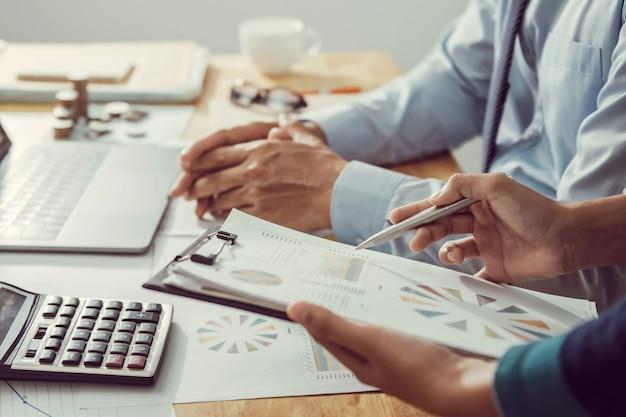 Zakenman die op kantoor werkt met behulp van een rekenmachine om het boekhoudconcept van de cijfersfinanciën te berekenen