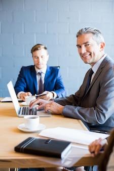 Zakenman die op laptop in een vergaderruimte werkt tijdens vergadering op kantoor