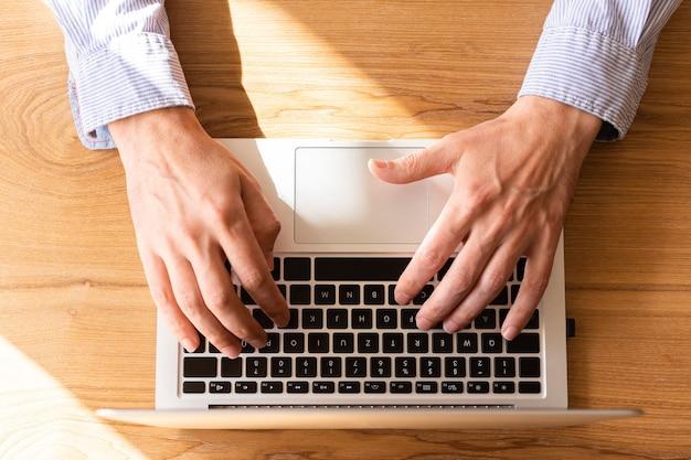 Zakenman die op laptop werkt, bovenaanzicht op mannelijke handen met behulp van laptop