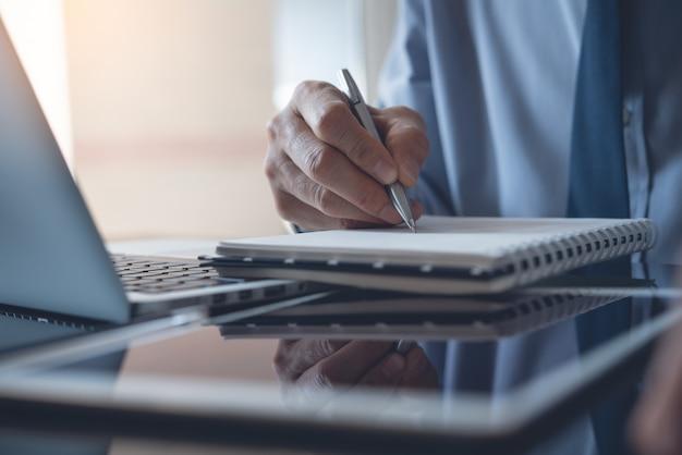 Zakenman die op laptop werkt en op notitieboekje in bureau schrijft