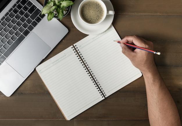 Zakenman die op leeg notitieboekje met laptop schrijft