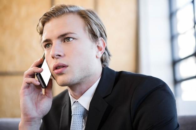 Zakenman die op mobiele telefoon in bureau spreekt