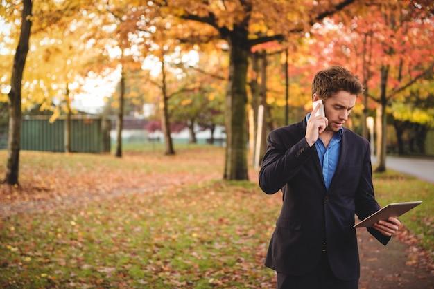 Zakenman die op mobiele telefoon spreekt en digitale tablet houdt