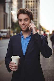 Zakenman die op mobiele telefoon spreekt en koffie houdt