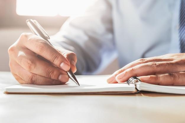 Zakenman die op notaboek schrijven in bureau
