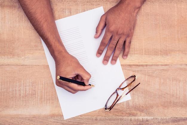 Zakenman die op papier bij bureau in bureau schrijft