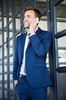 Zakenman die op smartphone in bureau spreekt