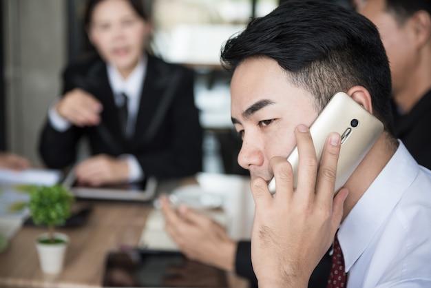 Zakenman die op smartphone in de vergadering spreekt.