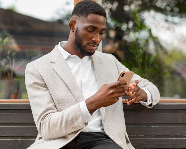 Zakenman die op smartphone kijkt