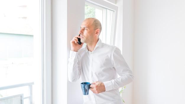 Zakenman die op smartphone spreken die door bureauvenster kijken