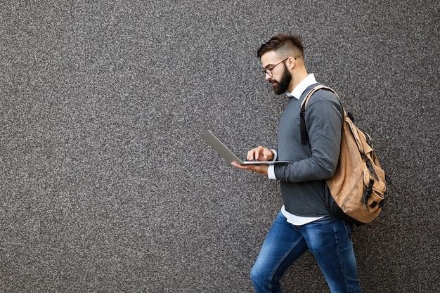 Zakenman die op straat loopt en zijn laptop vasthoudt, buiten aan het werk
