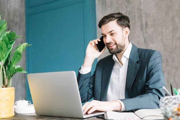 Zakenman die op telefoon dichtbij laptop spreekt