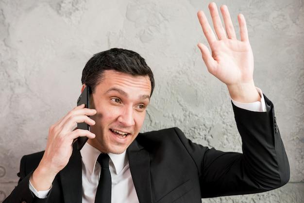 Zakenman die op telefoon en golvende hand spreekt