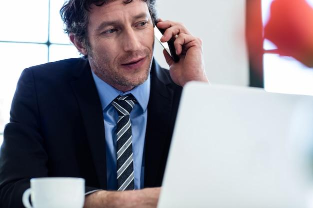 Zakenman die op telefoon spreekt en zijn laptop met behulp van