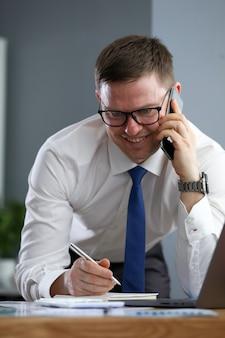 Zakenman die op telefoon spreken die info neerschrijven