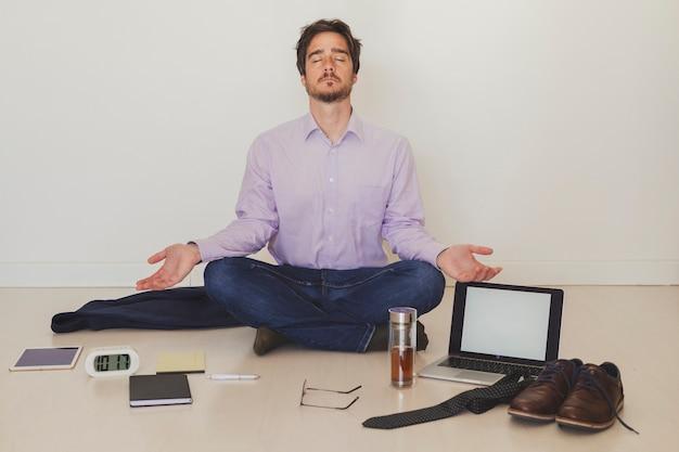 Zakenman die op vloer mediteren