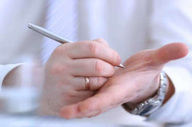 Zakenman die op zijn hand schrijft