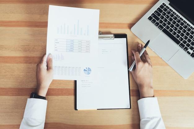 Zakenman die op zijn kantoor met documenten werkt en de nauwkeurigheid van informatie controleert.