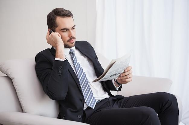 Zakenman die op zijn krant van de laaglezing telefoneren