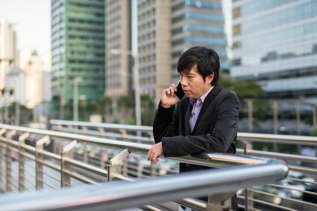 Zakenman die over telefoon in stad spreekt
