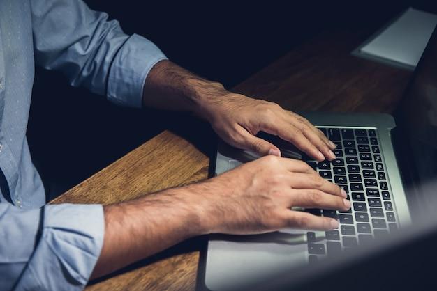Zakenman die overuren laat bij nacht blijven die met notitieboekjecomputer werken
